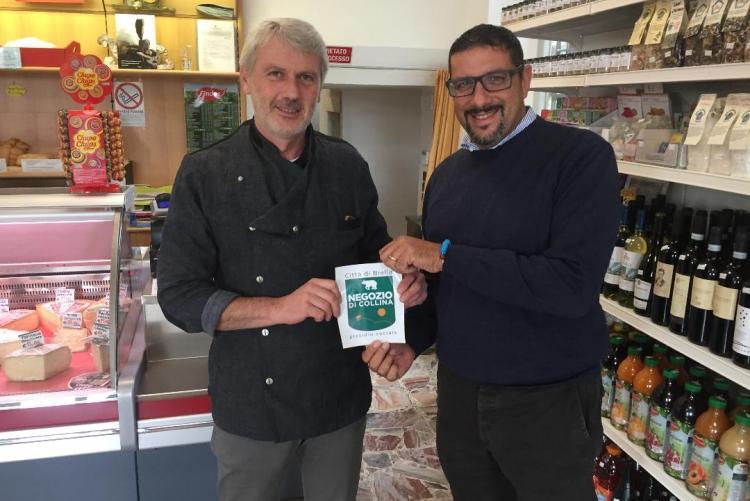 L'assessore La Malfa consegna l'adesivo dei negozi di collina a Giorgio Graziano dell'alimentari 'L Val di Vaglio